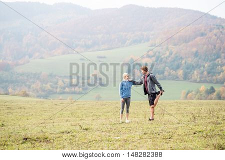 Two young beautiful runners in colorful autumn nature, stretching legs