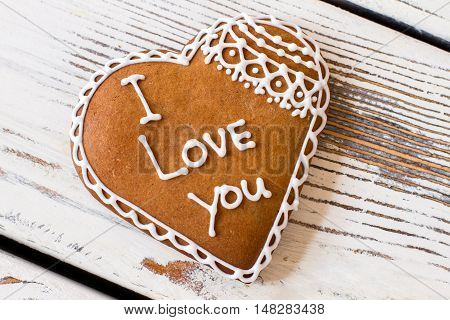 Cookie with inscription. Brown biscuit on wooden surface. Convey an important message. Dessert that tastes like love.