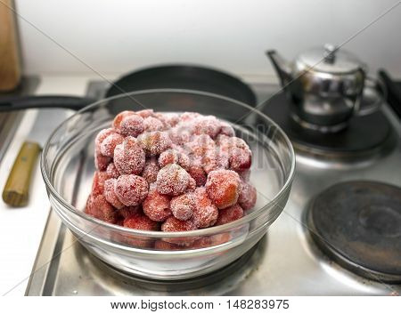 Defrosting strawberry in a glass bowl on a top of electric stove closeup interior shot