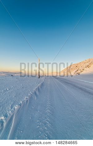 Winter road, the snow-covered slopes. Older inactive light poles.