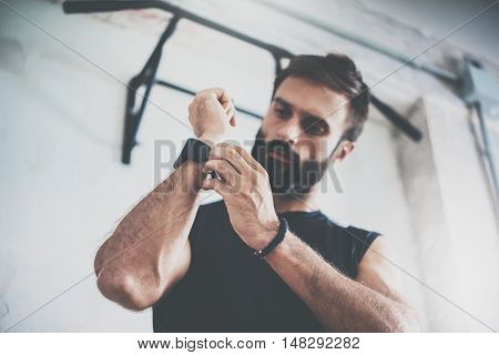 Young Bearded Sportive Man Workout Session Checks Fitness Results Smart Watch.Adult Guy Dress Sport Tracker Wristband Arm.Training hard gym.Horizontal bar background.Blurred