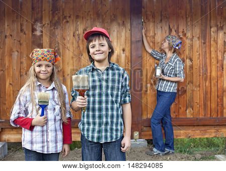 Kids helping their mother painting the wood shed - holding brushes
