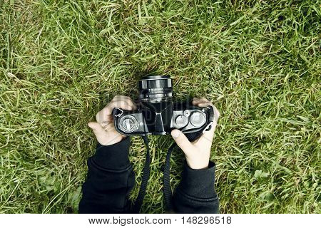 Hands holding camera on grass. Child blond boy with vintage photo film camera photographing outside