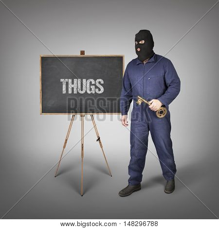Thugs text on blackboard with thief and key