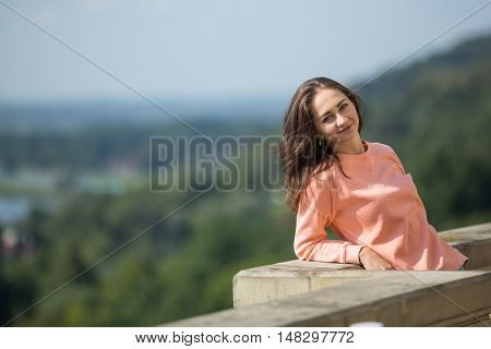 Cute young lady standing at the parapet.