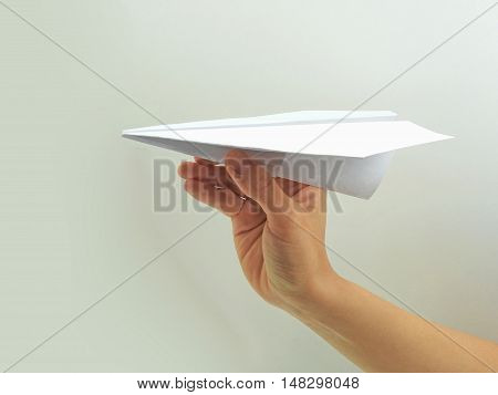 Paper plane in woman hand. Isolated on gray background.