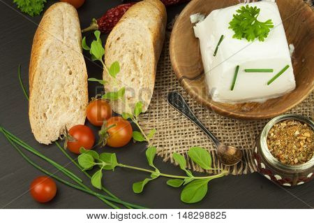 Goat cheese with fresh tomatoes on wooden table. Fresh cheese and pastries. Diet food. Goat cheese with vegetables.
