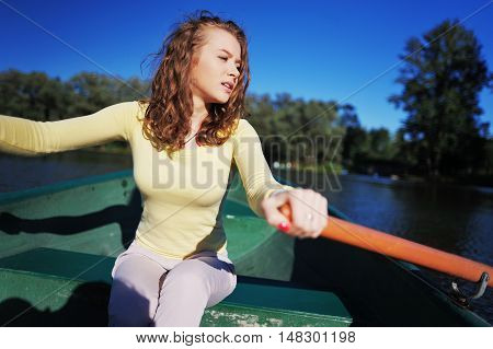 Beautiful young girl sitting at the oars and tired rowing in a wooden boat floating in the middle of the river
