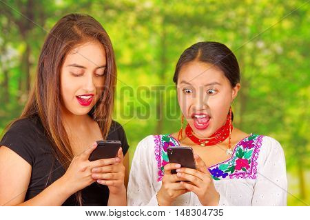 Two beautiful young women posing for camera, one wearing traditional andean clothing, the other in casual clothes, both pressing phones looking at mobile screens, park background.