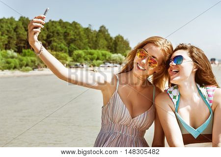Two attractive young girls in suglasses standing together, posing and doing selfie on the beach backdrop