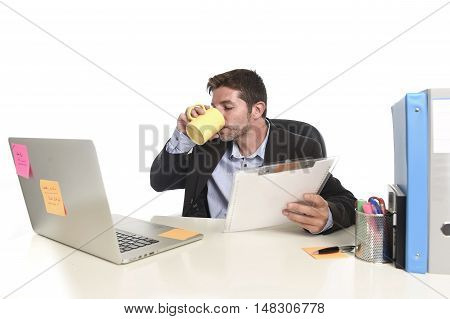 young attractive businessman working happy and confident at office reading file drinking coffee sitting on laptop computer desk in success business concept isolated in white background