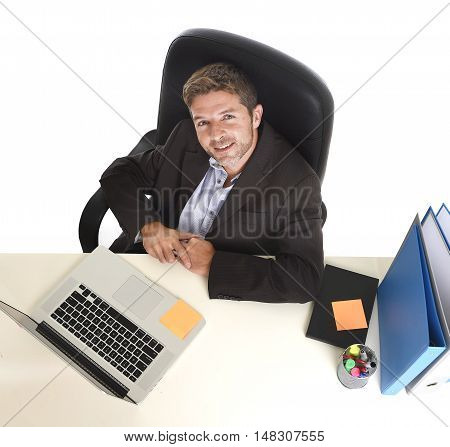 corporate portrait young attractive businessman happy and confident at office with paperwork file working on laptop computer desk smiling in success business concept isolated white background