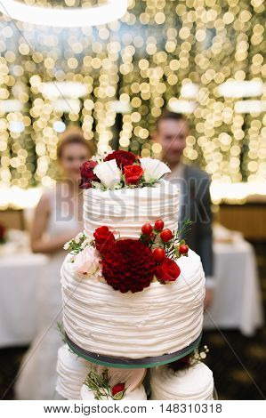 white tiered wedding cake with flowers and berries