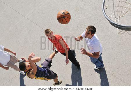 Grupo de jóvenes que jugando baloncesto al aire libre en la calle con sombras largas y pájaro ve perspectiva