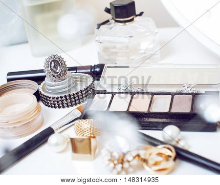Jewelry table with lot of girl stuff on it, little mess in cosmetic brushes, interior concept close up