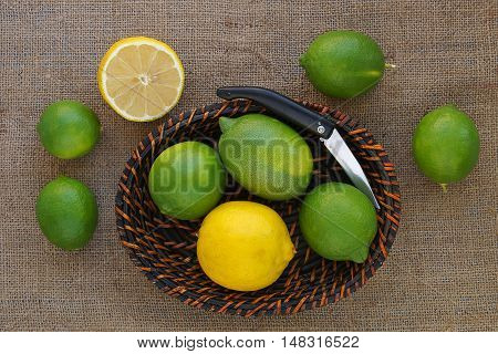 Green and yellow lemons in the basket and on the sack