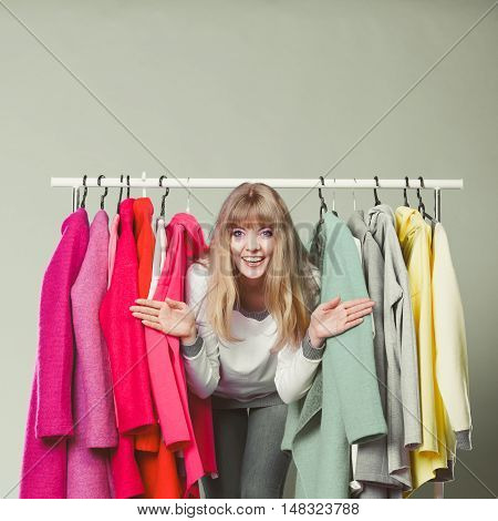 Pretty woman sneaking among clothes in wardrobe. Attractive young girl customer shopping in mall shop. Fashion clothing sale concept.