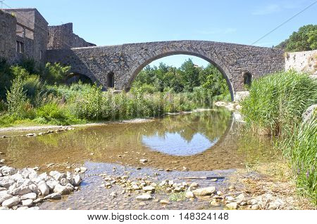 Vieux Bridge In Lagrasse And The Reflection In The River Making A Circle, France