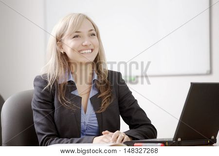 Portrait of a young smiling business woman using laptop at office. Business suit, business concept/Successful business woman working at the office