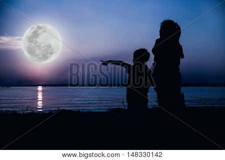 Silhouette of mother and son enjoying view at riverside boy point to full moon on blue sky background. Happy family spending time together. Cool colors tone. The moon were NOT furnished by NASA.