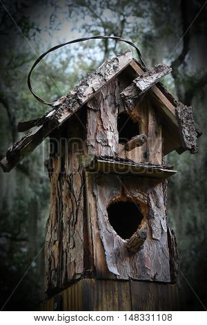 Eerie Weathered Bird House battered by woodpeckers