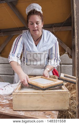 A woman demonstrates traditional paper making with pulp and a screen