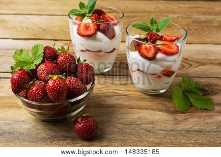 Ripe strawberries and layered cream cheese dessert on wooden background. Whipped cream with fresh strawberry.
