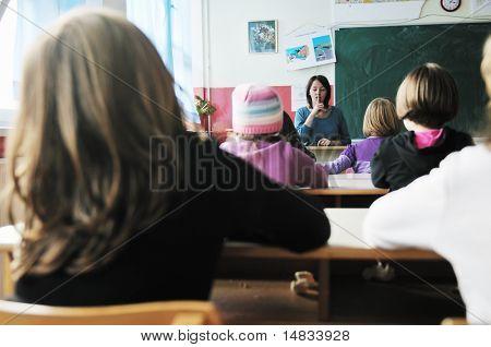 glückliche junge Lehrerin Frau an der Elementary School unterrichten und den Unterricht zu Gruppe von jungen intelligenten c