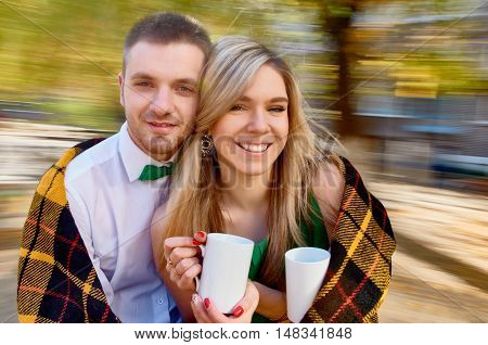 happy ypung couple with a cups. background with natural motion blur