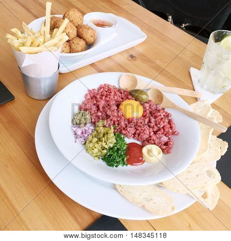 Beautiful beef tartare with egg yolk mustard ketchup scallions red onions cornichons capers and bread on a white plate in a Sao Paulo Brasil restaurant. On table with croquettes fries and caipirinha.
