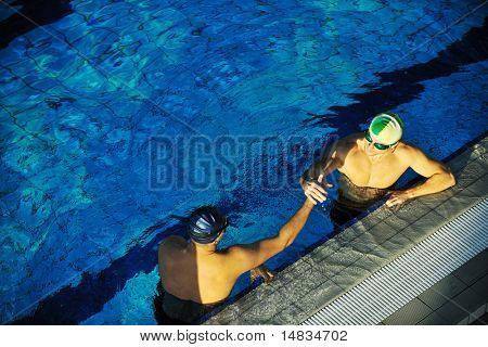 win competiotion and swimming race concept with two freiend who handshaking in pool