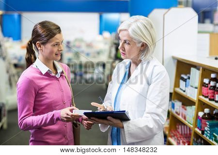 Pharmacist writing prescriptions for customer on clipboard in pharmacy