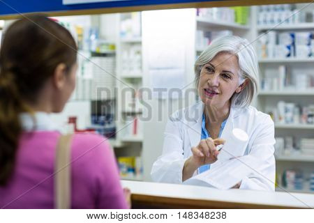 Pharmacist assisting the bottle of drug to customer in pharmacy