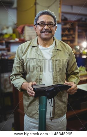 Portrait of smiling shoemaker examining a shoe in workshop