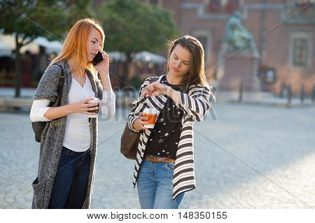 Two cute College co-eds are on an empty cozy square. Girls are holding paper cups with coffee. Redheaded girl speaks on a mobile telephone. Her friend looks at his watch.