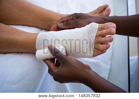 Doctor bandaging patients leg in hospital