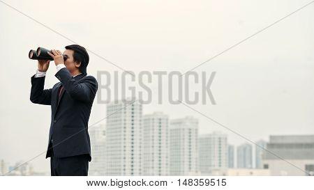 Business executive looking at city through binocular