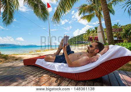 Man reading book under oconut palm tree on Beautiful Tropical beach