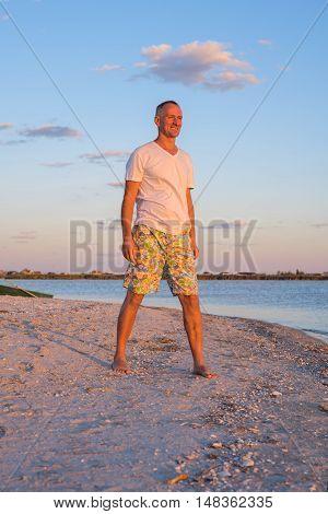 Joyful smiling man on the beach enjoying the sunset. A wonderful moment of encounter with the sea.