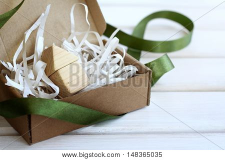 concept small wooden house in open box with green ribbon unleashed / idea ecological house in a gift