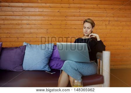 Female proud economist is watching world news via net-book while is waiting her client in informal settings. Woman successful freelancer is searching new projects in the network via laptop computer