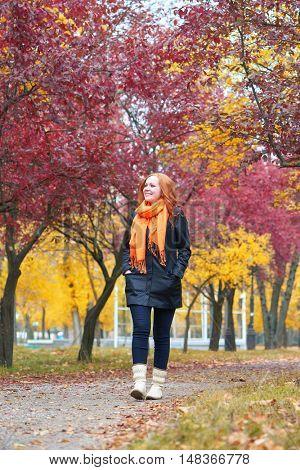 girl walk on footpath in city park, fall season