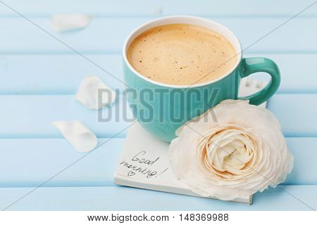 Coffee cup with spring flower and notes good morning on blue rustic background. Breakfast on Mothers day or Womens day.