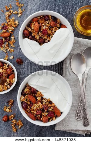 Homemade yogurt bowl with granola on black table. Healthy and diet breakfast, top view. Flat lay.