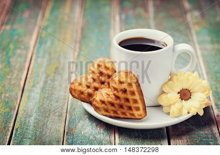 Waffle biscuits in shape of heart with cup of coffee and flower on rustic background for Valentines day, vintage toned.