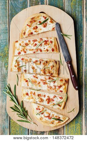Tart Flambe or Flammkuchen on wooden cutting board. Traditional Alsatian pie. Rustic style, top view.