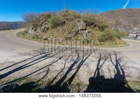 Mountain s-shape curved road, harpin bend wide angle with tree shadows on a bright day