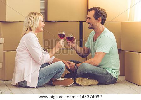 Beautiful mature couple in casual clothes is clanging glasses of wine and smiling while sitting on the floor among boxes moving to the new apartment