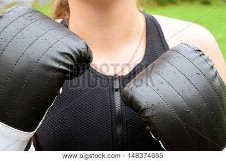 Young woman with black boxing gloves closeup.