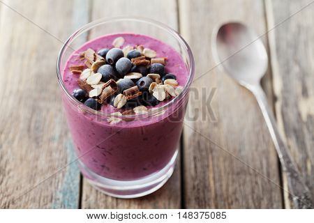 Healthy breakfast of smoothie dessert, yogurt or milkshake with frozen berry and oats decorated grated chocolate on wooden vintage table.